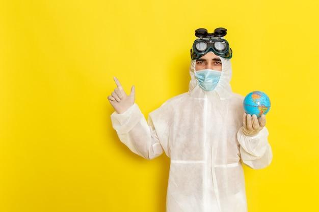 Trabalhador científico masculino de vista frontal com terno especial segurando o globo redondo na mesa amarela