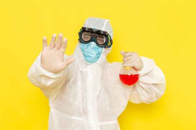 Trabalhador científico masculino de vista frontal em traje de proteção especial, segurando o frasco com solução vermelha na mesa amarela