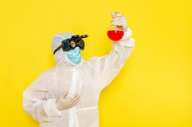 Trabalhador científico masculino de vista frontal em traje de proteção especial segurando o frasco com solução vermelha na superfície amarela