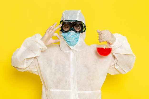 Trabalhador científico masculino de vista frontal em traje de proteção especial, segurando o frasco com solução vermelha posando na superfície amarela