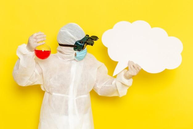 Trabalhador científico masculino de vista frontal em traje de proteção especial, segurando o frasco com uma grande placa branca de solução vermelha na mesa amarela