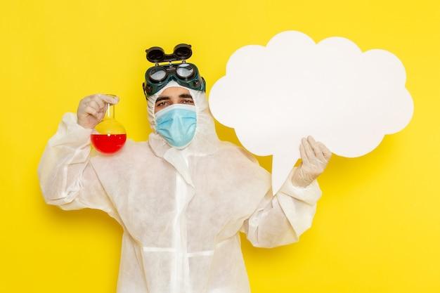 Trabalhador científico masculino de vista frontal em traje de proteção especial, segurando o frasco com uma grande placa branca de solução vermelha na superfície amarela