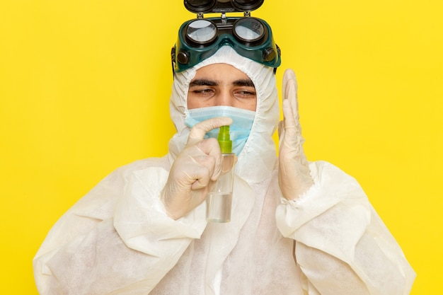 Trabalhador científico masculino de vista frontal em traje de proteção especial segurando spray e usando-o na superfície amarela