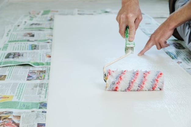 Trabalhador colando papéis de parede.