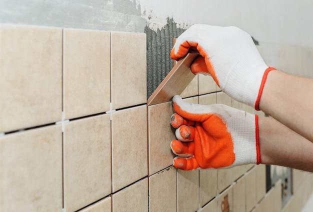Trabalhador coloca telhas na parede da cozinha. suas mãos estão colocando o ladrilho no adesivo.