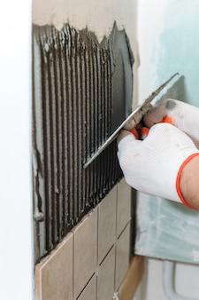 Trabalhador, colocando azulejos na parede da cozinha.