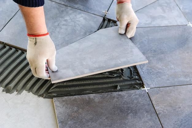 Trabalhador colocando ladrilhos na varanda