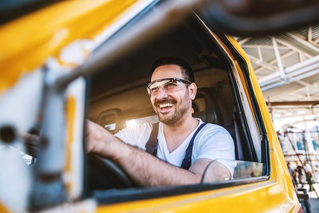 Trabalhador com barba bonito sorridente dirigindo veículo no canteiro de obras.