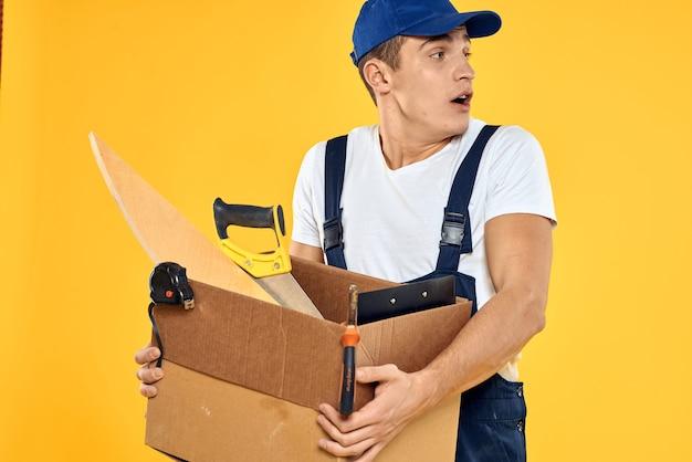 Trabalhador com caixa em fundo amarelo do carregador de ferramentas manuais. foto de alta qualidade
