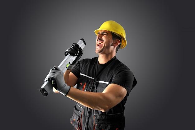 Trabalhador com capacete amarelo e cara louco