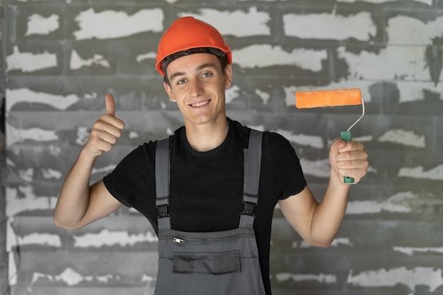 Trabalhador com capacete capacete perto de uma parede de pedras. segura o rolo nas mãos levanta o polegar