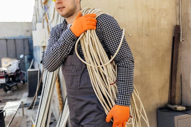 Trabalhador com capacete carregando corda