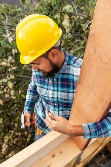 Trabalhador com capacete construindo com madeira
