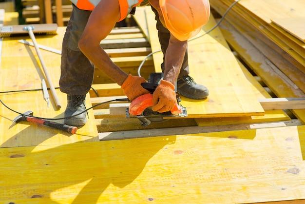 Trabalhador com capacete de segurança serrando um close-up de placa de madeira