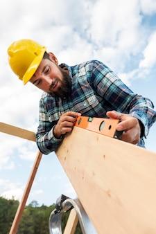 Trabalhador com capacete e nível verificando a madeira do telhado