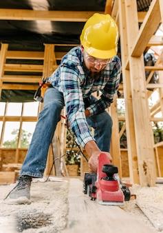 Trabalhador com capacete lixando pedaço de madeira