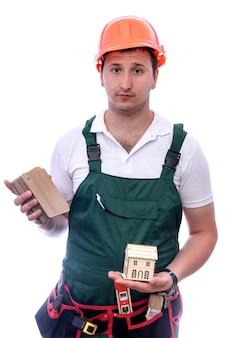 Trabalhador com capacete segurando um modelo de casa de madeira