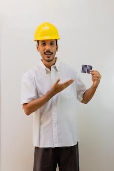 Trabalhador com capacete segurando um painel solar fotovoltaico isolado no fundo branco.