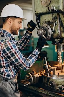 Trabalhador com capacete trabalhando com construções de metal na fábrica