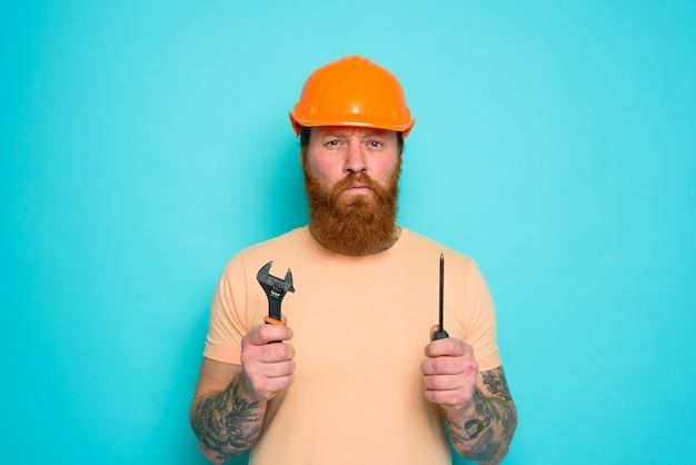 Trabalhador com chapéu amarelo está confuso sobre seu trabalho