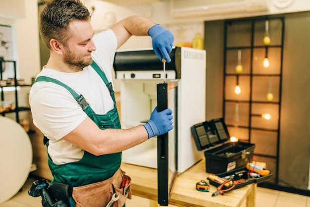 Trabalhador com chave de fenda conserta porta da geladeira