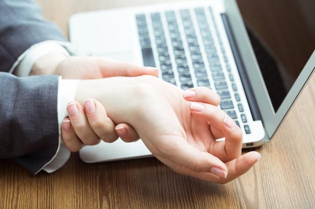 Trabalhador com dor no pulso devido ao trabalho árduo no escritório