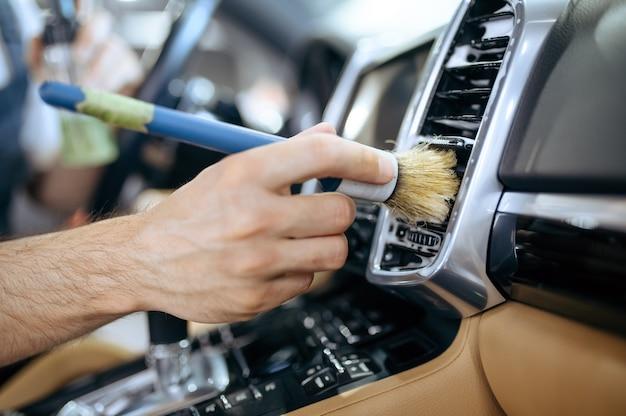 Trabalhador com escova limpa a grade do duto de ar do carro, lavagem a seco e detalhamento.