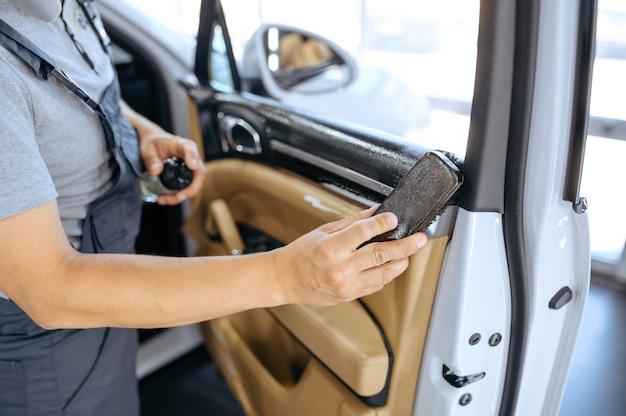 Trabalhador com escova limpa o acabamento da porta do carro, lavagem a seco e detalhamento.