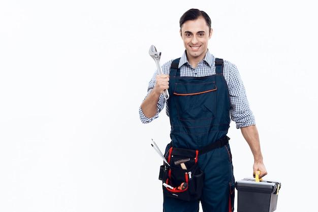 Trabalhador com ferramentas e chave no fundo branco.