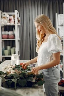 Trabalhador com flores. mulher faz um buquê. linda garota trabalhando