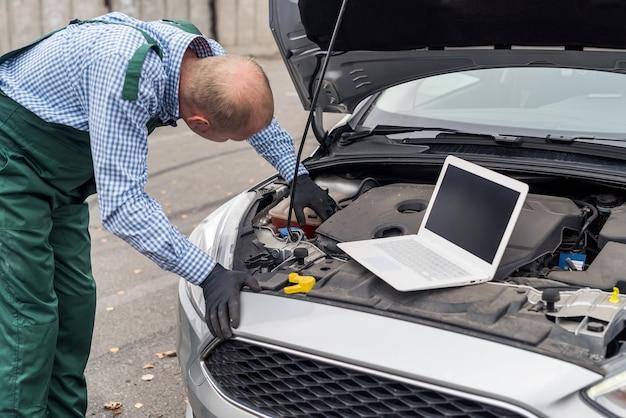 Trabalhador com laptop fazendo diagnóstico do motor do carro