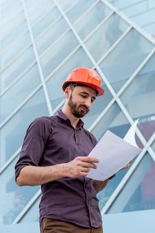 Trabalhador, com, laranja, capacete, leitura, esquemático