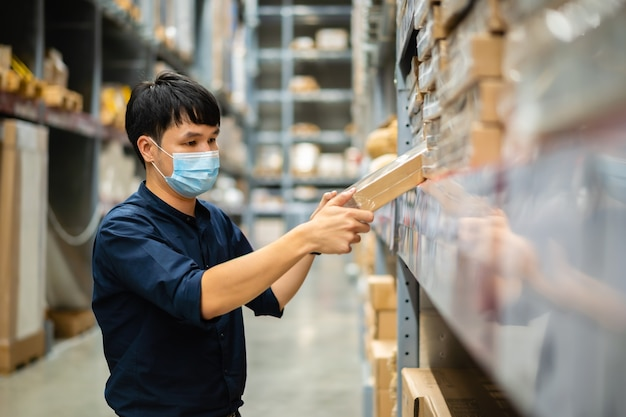Trabalhador com máscara médica verificando o estoque no depósito durante a pandemia de coronavírus