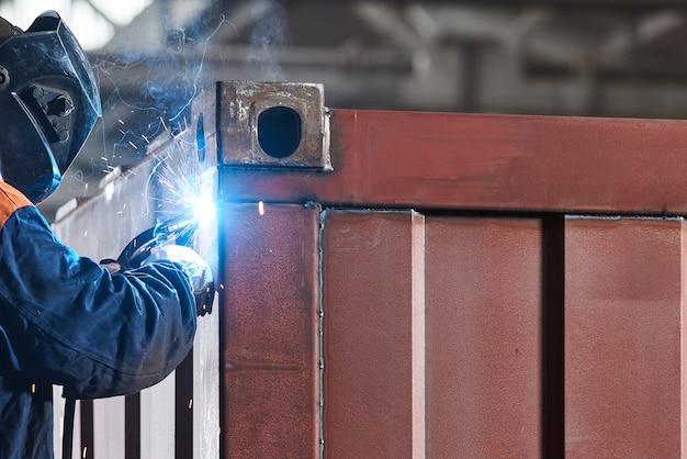 Trabalhador com máscara protetora e luvas soldando metal closeup Foto Premium