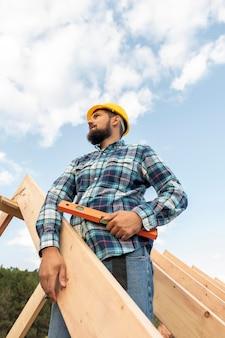 Trabalhador com nível de construção do telhado da casa
