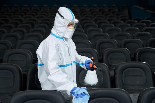 Trabalhador com roupas protetoras limpando a sala do cinema