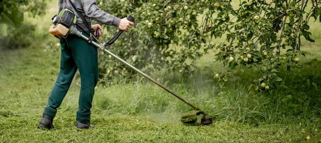Trabalhador com um cortador de gás nas mãos, cortando a grama na frente da casa. trimmer nas mãos de um homem