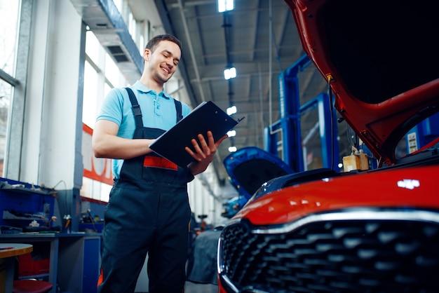 Trabalhador com uma lista de verificação fica no veículo com capô aberto, posto de gasolina do carro.