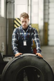 Trabalhador com uma roda. substituição da roda. homem de uniforme