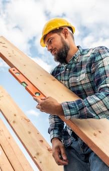 Trabalhador com verificação de nível da madeira do telhado