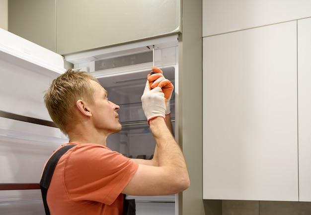 Trabalhador consertando a geladeira embutida nos móveis da cozinha