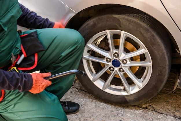 Trabalhador consertando a roda do carro com a chave inglesa close-up