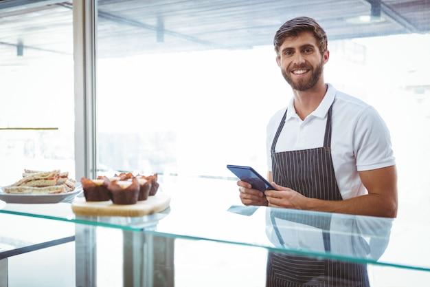 Trabalhador considerável posando no balcão com um tablet