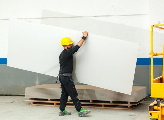 Trabalhador constrói uma parede de gesso cartonado.