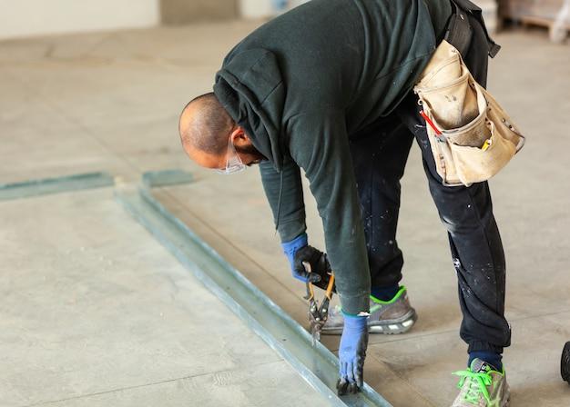 Trabalhador constrói uma parede de gesso cartonado