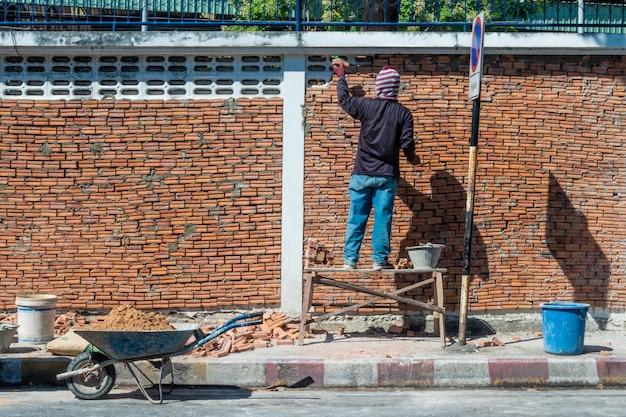 Trabalhador constrói uma parede de tijolos