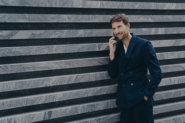 Trabalhador corporativo masculino, vestido com um terno preto formal, com a mão no bolso, conversando ao telefone