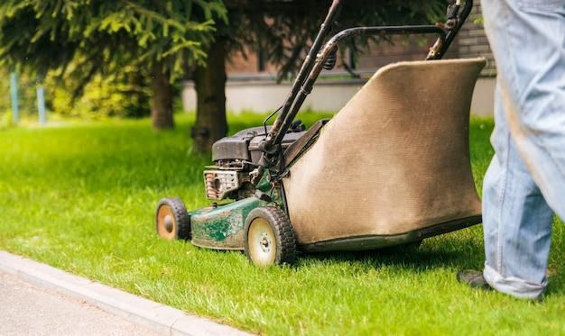 Trabalhador corta a grama com um cortador de grama.