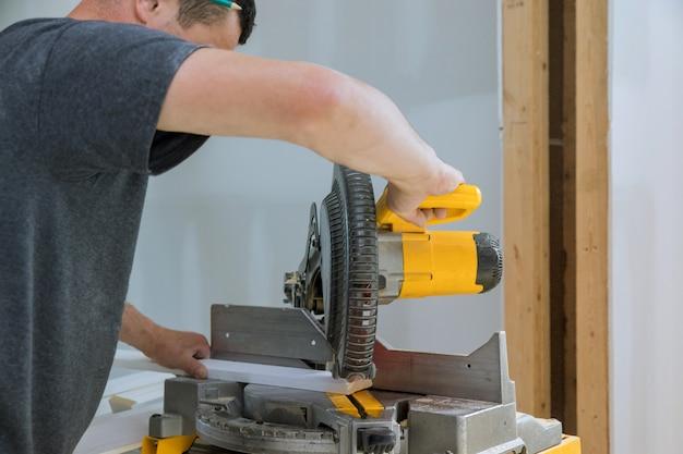 Trabalhador corta rodapé de madeira na serra elétrica