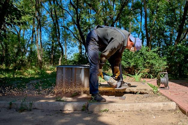 Trabalhador cortando metal com moedor, ao ar livre